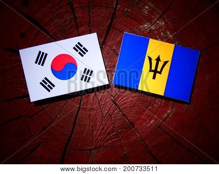 Barbados Flag With South Korean Flag On A Tree Stump Isolated
