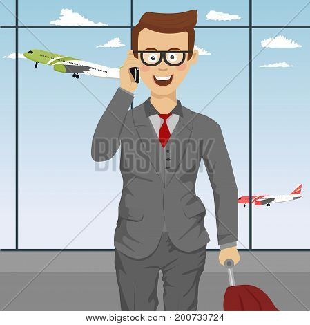 Successful cute businessman with glasses and suitcase talking on the phone at the airport
