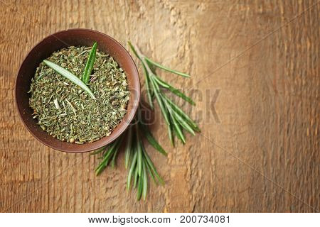 Bowl with dried herbs and fresh rosemary on table