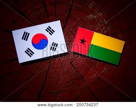 Guinea Bissau Flag With South Korean Flag On A Tree Stump Isolated