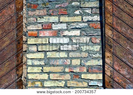 Brown background of bricks and wooden boards on the wall