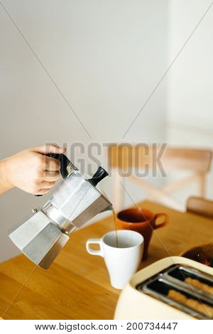 Girl hands close up pouring coffee in a Cup on a wooden table in the morning.