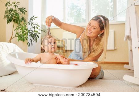 The mother bathes play the baby child in the bathroom in the room.