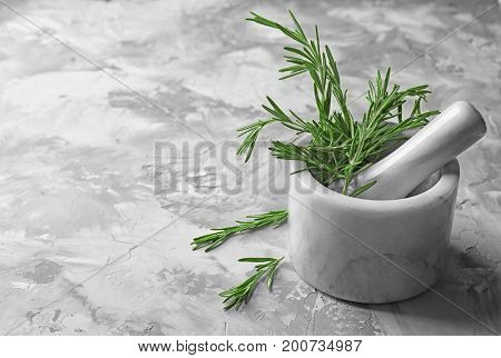 Mortar with fresh rosemary on table