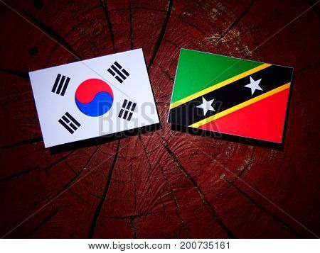 Saint Kitts And Nevis Flag With South Korean Flag On A Tree Stump Isolated