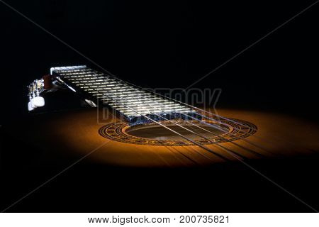 Abstract closeup of a guitar in the dark only partial illuminated.