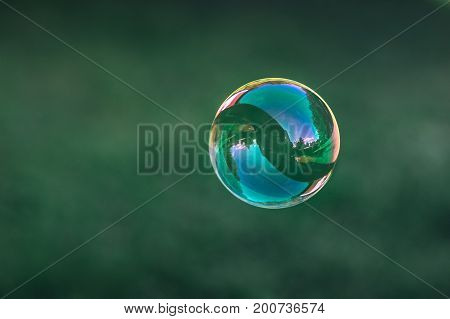 Close up of flying soap bubble with great reflections. Flying over green background