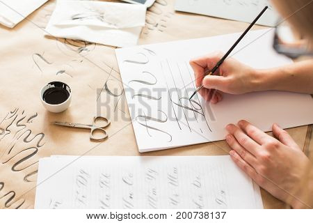 graphic design, handwriting, creation concept. tender little hands of female painter inscribing ornamental decorated letters on the white lined paper with help of thin tip of the brush and black ink