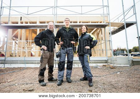 Carpenters Standing With Hands On Hips At Construction Site