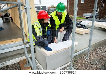 Carpenters With Plan Sitting At Construction Site
