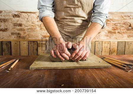 potter, workshop, ceramics art concept - closeup on male hands modeling raw clay, a ceramist work with material on wooden table with fireclay and sculpting tool set, front view