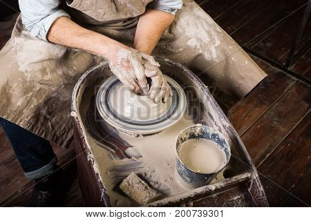 pottery, workshop, ceramics art concept - closeup on working potter's wheel with raw clay and man's hands, a male sculpt a utensil with fingers, master in apron, top view, close