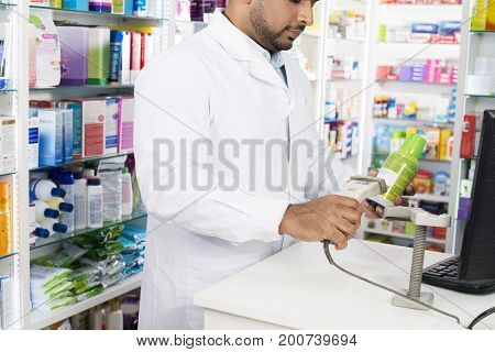 Chemist Scanning Barcode Of Product At Checkout Counter
