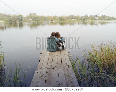 Romantic couple on the edge of village pier before green lake or bog