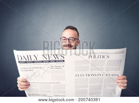 Young smart businessman reading daily newspaper