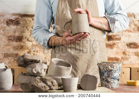 pottery, workshop, ceramics art concept - male ceramist stand at a workplace and wearing clay-stained apron, young craftsman's hands holding unbaked jug, workplace with fireclay and unfinished cups