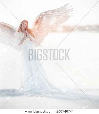 Woman angel with wings in the winter. Snow angel standing in the snow the Keeper of winter a fabulous image