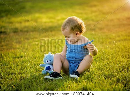 Cute little girl is played with a toy in the park on the grass