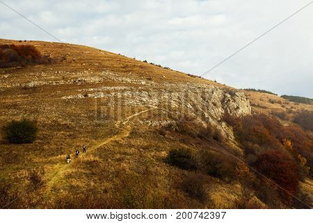 Group of three hikers going up the trail path. Wide shot of three backpackers climbing a mountans. Beautiful autumn scenery