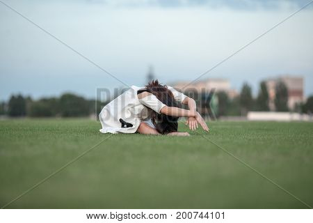 Ballerina in white dress bent down to her feet sitting on lawn.