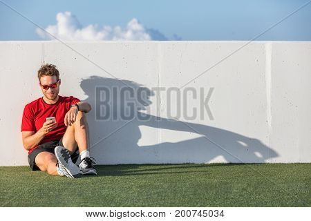 Fitness sport man using mobile phone app after workout training relaxing sitting on outdoor grass post run.