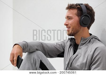 Man listening to music mobile phone app wearing headset sitting at home. Healthy lifestyle sport athlete using smartphone on jogging break outdoors relaxing in casual clothing.