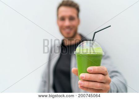 Health man drinking weight loss green smoothie drink. Hand holding plastic cup of vegetable juice, healthy food diet eating lifestyle.