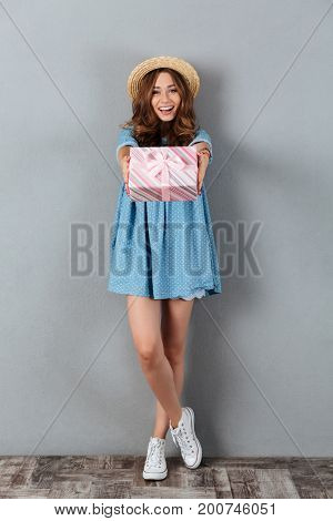 Picture of smiling young pretty woman standing over grey wall wearing hat holding gift. Looking camera.