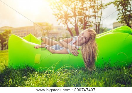 Young Woman Resting On An Air Sofa In The Park.