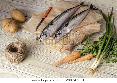 Carrots, potatoes, green onions and raw mackerel on a wooden table close-up