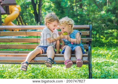 Toddlers Boy And Girl Sitting On A Bench By The Sea And Eat An Apple