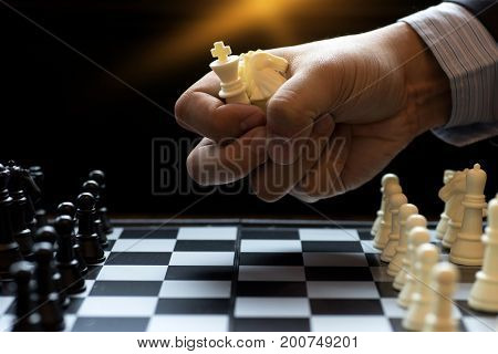 Businessman Grip Many Chess Piece In The Hand  To Play Chess