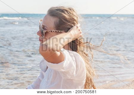 A young woman in sunglasses holds a hand to her hair fluttering in the wind near the sea. The concept of a free way of life.