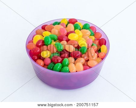 Violet Plastic Round Medium Size Bowl For Loose Products Filled With Colored Small-sized Sweets Isol