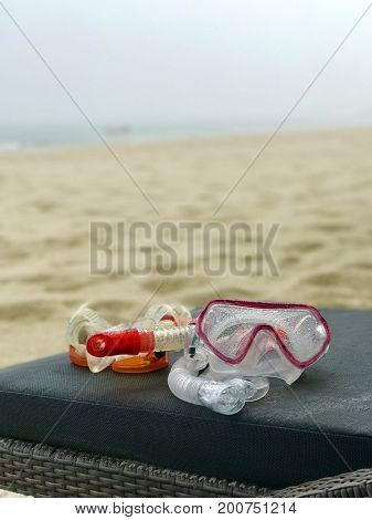 Snorkel and diving mask snorkeling equipment on a deckchair on a white sand beach and sea view