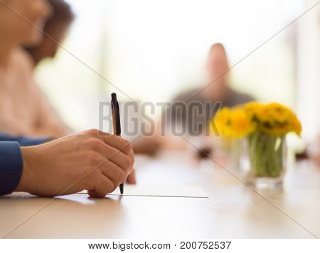 close up shot of Business man hand holding pen writing on papers at seminar or signing contract making a deal
