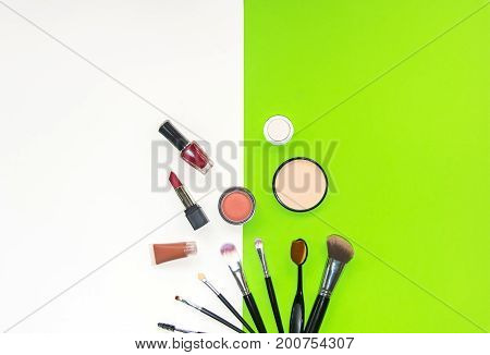 Cosmetics and fashion background with make up artist objects: lipstick eye shadows mascara eyeliner concealer nail polish. Green and white background. Lifestyle Concept