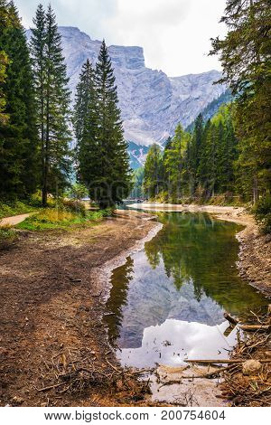 Stroll around the beautiful alpine lake Lago di Braies. Travel to South Tyrol, Italy. The concept of walking and eco-tourism