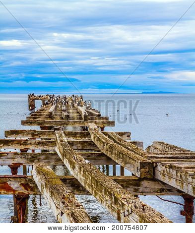 South of South America.  Rusted and destroyed remains of the sea mooring. The legendary Strait of Magellan. Cloudy morning. The concept of extreme and active tourism