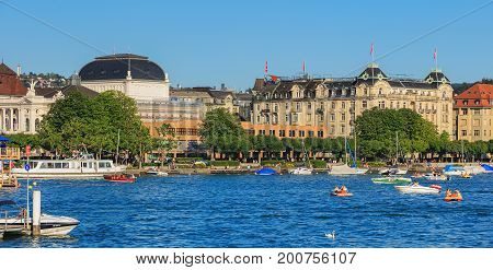Zurich, Switzerland - 20 July, 2016: Lake Zurich, buildings of the city of Zurich along the lake, people in boats and on the embankment of the lake. Lake Zurich is a lake in Switzerland, extending southeast of the city of Zurich.