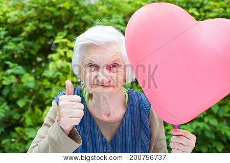 Picture of a cute elderly lady celebrating birthday with a heart shaped balloon in the park outdoor