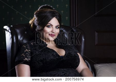 Plus size fashion model in black evening dress fat woman on luxury interior professional make-up and hairstyle