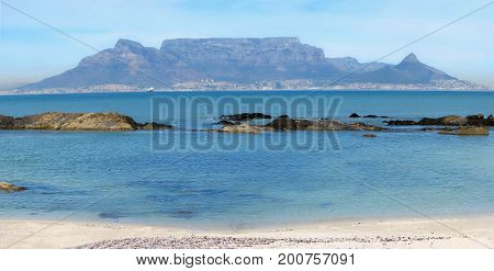 FROM BLOUBERG STRAND, CAPE TOWN, SOUTH AFRICA, WITH THE CALM BLUE SEA IN THE FORE GROUND AND TABLE MOUNTAIN IN THE BACK GROUND