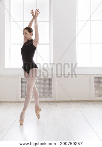 Beautiful graceful ballerina in black practicing ballet positions near large window in light hall. Ballet class training, classical dancer side view, copy space