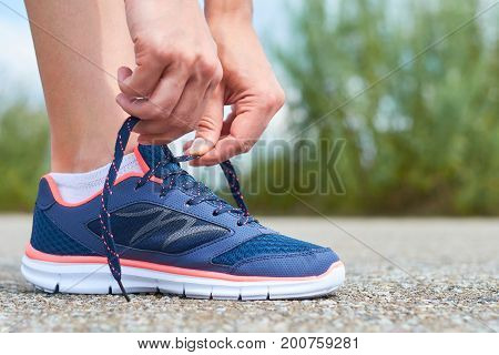 Girl ties up shoelaces in sneakers on road while jogging, legs and sneakers.