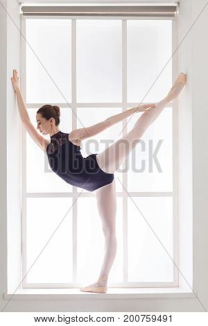Young graceful ballerina in black leotard making arabesque in a window case, side view, copy space