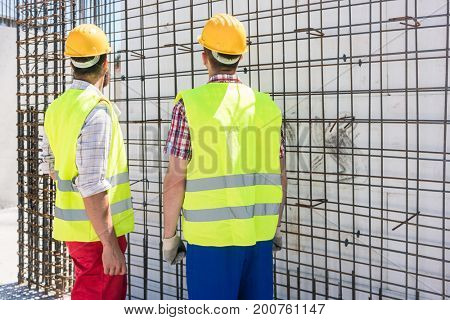 Two blue-collar workers wearing safety equipment, while checking the durability of the steel structure for the reinforcement of the walls of a building under construction