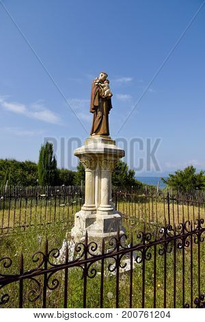statue of Saint Anthony of Padua surrounded by a grid fence in the Saint-Honorat island, France