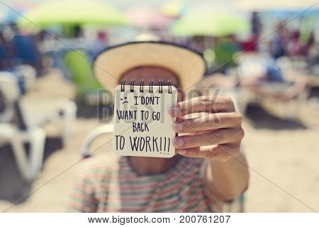 closeup of a young man in the beach showing a spiral notepad with the text I dont want to go back to work handwritten in it
