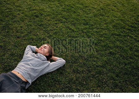 Beautiful young european woman lays down on grass and rests in summer day